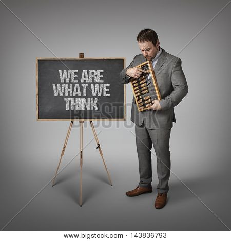 We are what we think text on blackboard with businessman and abacus