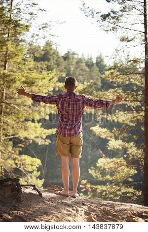 Young man enjoing fresh air in forest standing arms spread wide