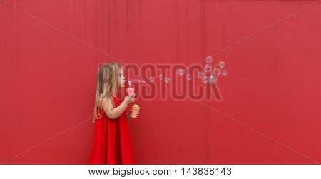 Blond girl child in red dress on a background of the red wall blows bubbles.