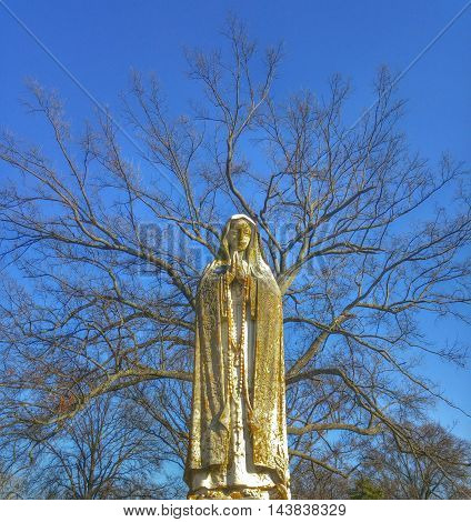 Nun sculpture, with rosary standing in front of trees