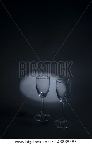 two glasses in dark colors on a black background