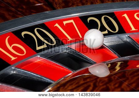 New Year 2017 classic casino roulette wheel with red sector seventeen 17 and white ball and sectors 20 16 18