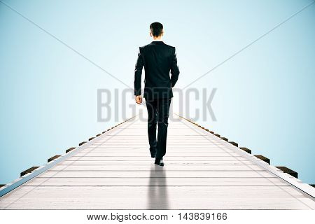 Businessman walking on wooden pier. Blue background with abstract sunlight. Success concept