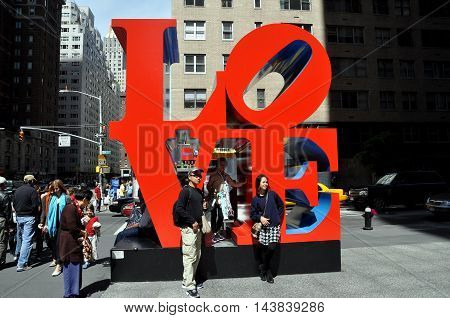 New York City - April 24 2010: Tourists pose in front of the LOVE sculpture by Robert Indiana on Avenue of the Americas in midtown Manhattan