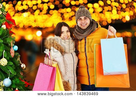 Beautiful couple with colorful bags on blurred city lights background. Winter holiday and christmas shopping concept.