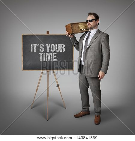 Its your time text on blackboard with businessman holding radio