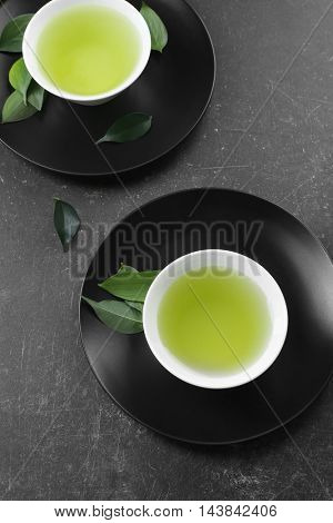 Cups of fresh matcha tea on grey background