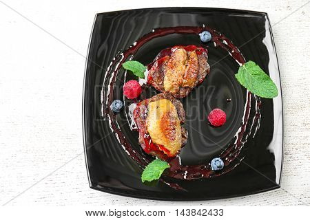 Juicy meat with sweet sauce on black plate
