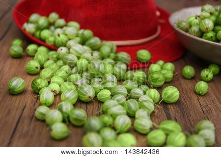 Gooseberries with hat on table