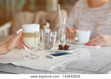 Woman hands holding glass of latte in cafe