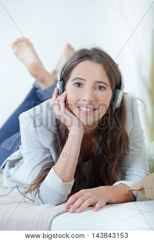 Girl with headphones layed on couch