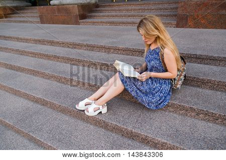 Young beautiful happy girl student sitting on the steps under the campus, university, school