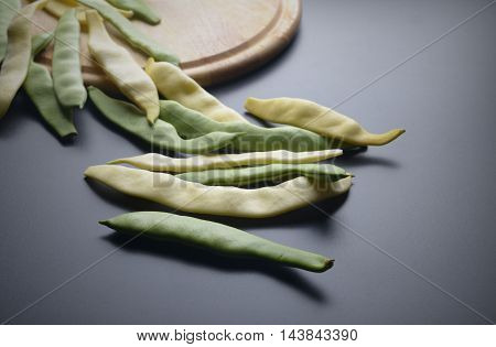 Yellow and green beans on a cutting board black background.