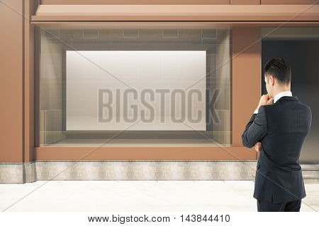 Thoughtful businessman looking at showcase with large billboard in daylight. Mock up 3D Rendering