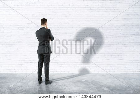 Thinking businessman with question mark shadow in room with white brick wall and concrete floor