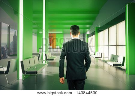 Businessman walking in green lobby interior with reception desk and New York city view