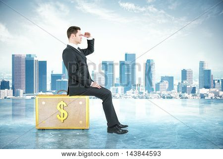Businessman looking into the distance while sitting on dollar suitcase. City background