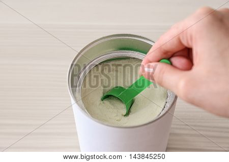 Woman hand is preparing baby formula on wooden table