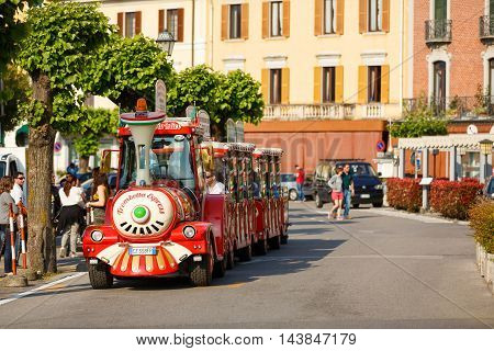 Bellagio Italy - May 06 2016: Some people have fun to ride on the tourist train on a street of resort