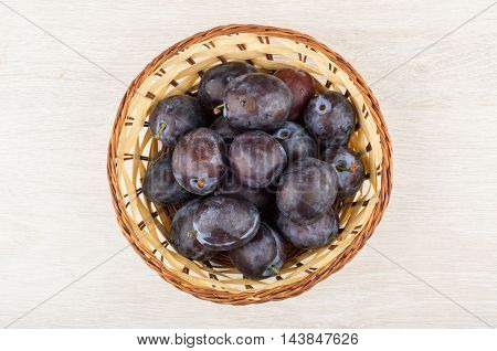 Wicker Basket With Ripe Plums On Wooden Table