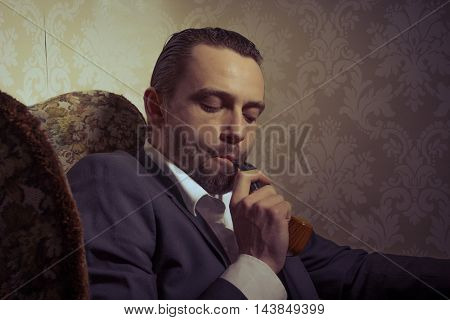 Young handsome and elegant man sitting in chair and smoking a pipe isolated over vintage background