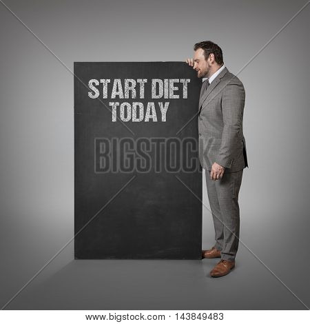 Start diet today text on blackboard with businessman standing side