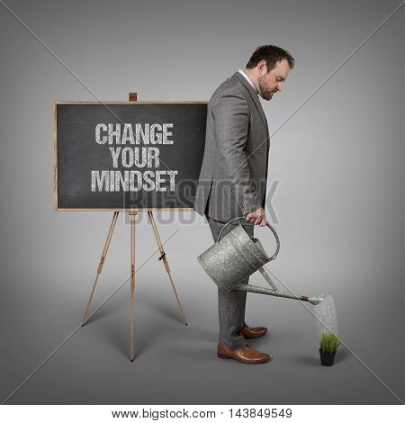 Change your mindset text on  blackboard with businessman watering plant