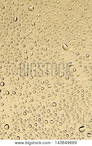 Water drops on a background of sand-yellow glass. Texture background.