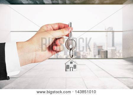 Businessman holding keys on concrete interior background. Real estate and mortgage concept