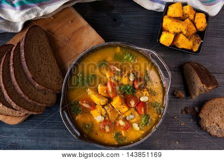 Pumpkin soup with tomatoes and herbs in a rustic style. Top view, close view, copy space