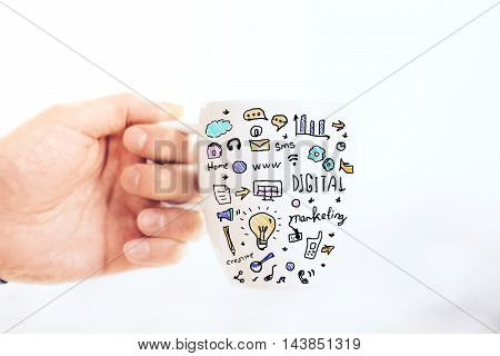 Male hand holding mug with business drawing on light background. Close up Success concept
