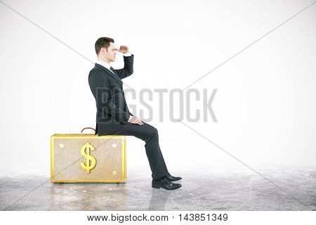 Businessman looking into the distance while sitting on dollar suitcase. White background