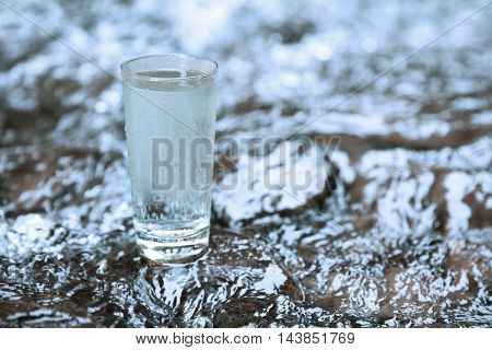 Glass of water on water background