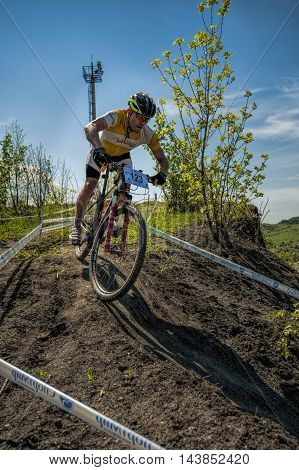 KHVALYNSK - MAY 7, 2016: Male cyclist descends from the slope at XCE eliminator track championship 'Match of Russian cities' on May 7, 2016 in Khvalynsk, Saratov region, Russia.