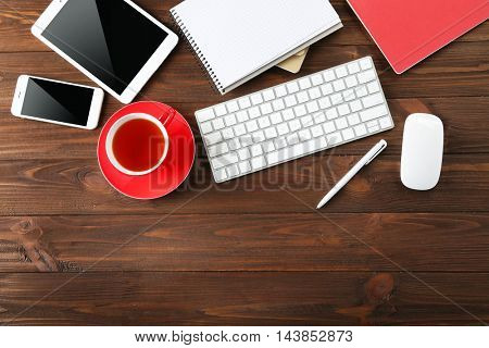 Modern workplace with cup of tea, top view