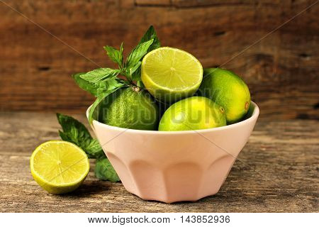 Lemons and limes in a bowl on a wooden table