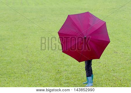 Little boy holding red umbrella. Green grass background. Outdoor. Back view
