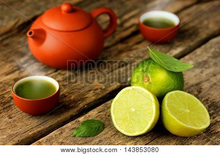 Matcha green tea fresh limes tea leaves on an old rustic wooden table. Selective focus