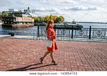 Fashionable woman in winter coat walking at autumn park.