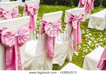 Wedding chairs with pink bows on the grass