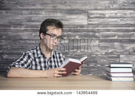 Smart young man in glasses reading reading at wooden table with book stack. Textured wooden wall in the background