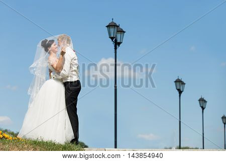 Newlyweds Laughing And Hugging Against The Sky