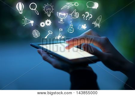 Closeup of hands using tablet with abstract business and success sketches