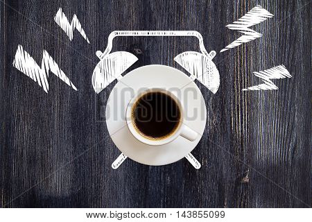 Top view of ringing coffee cup alarm clock sketch on dark wooden desktop. Time management concept