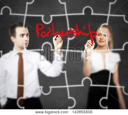 Business man and woman writing partnership text on abstract concrete background with puzzle piece pattern