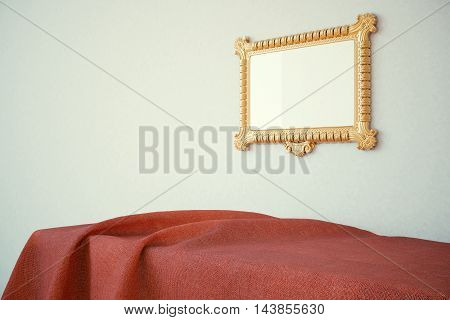Ornate golden picture frame hanging above surface covered with red cloth on concrete wall background. Mock up 3D Rendering