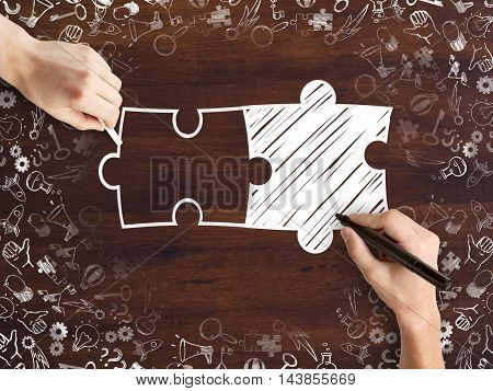 Male hands drawing puzzle pieces and success icons sketch on wooden desktop. Business partnership concept