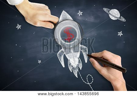Male hands drawing and holding magnifier over space ship sketch with red dollar sign. Chalkboard background. Start up concept
