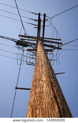 Photo of wooden electricity pylon with blue sky