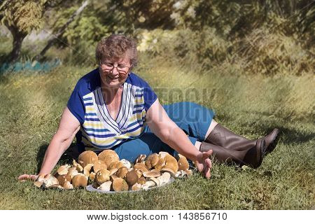 Elderly woman sitting on the grass with a pile of white mushrooms